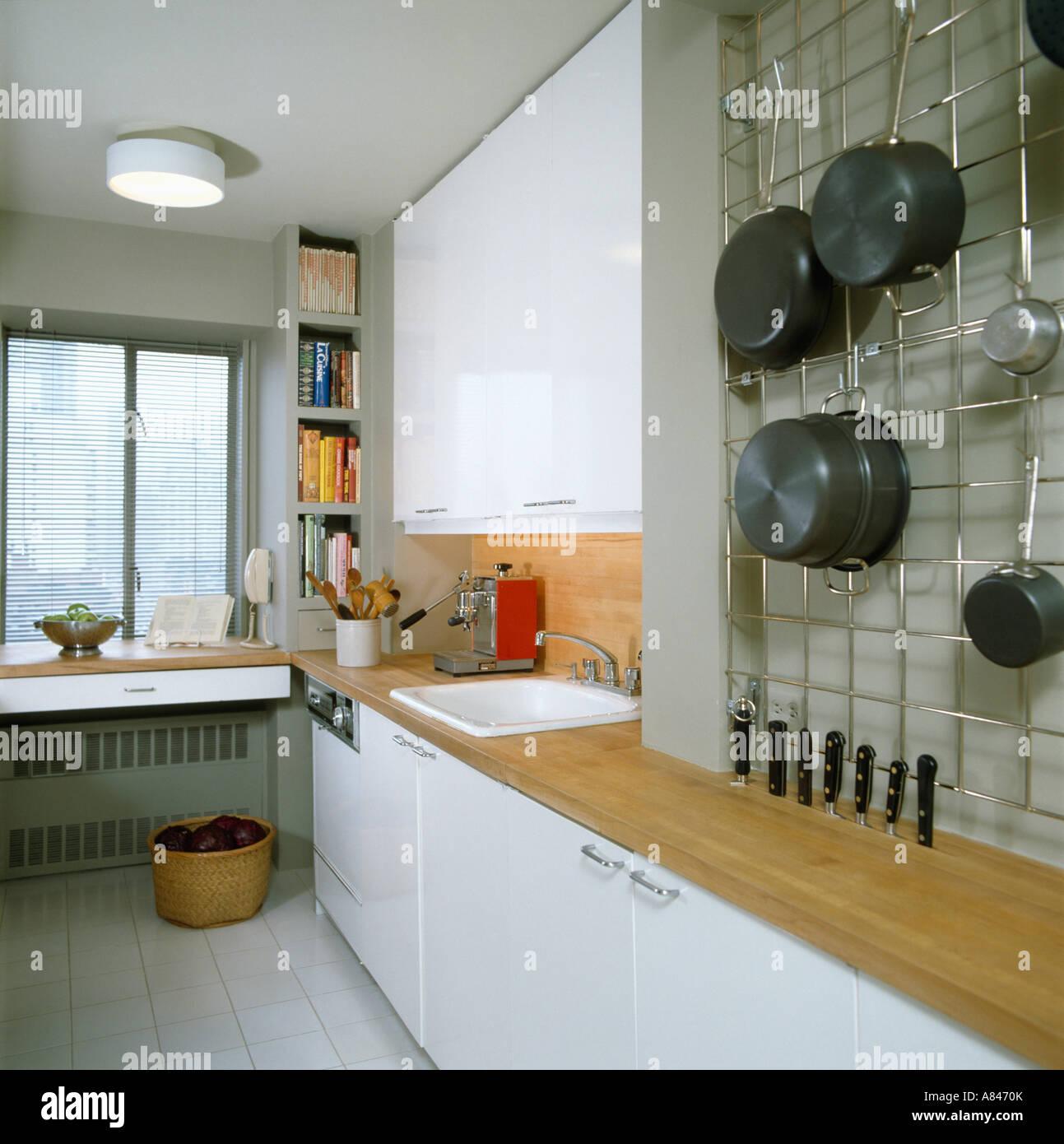 Attirant Saucepans Stored On Wire Wall Rack In Modern White Galley Kitchen