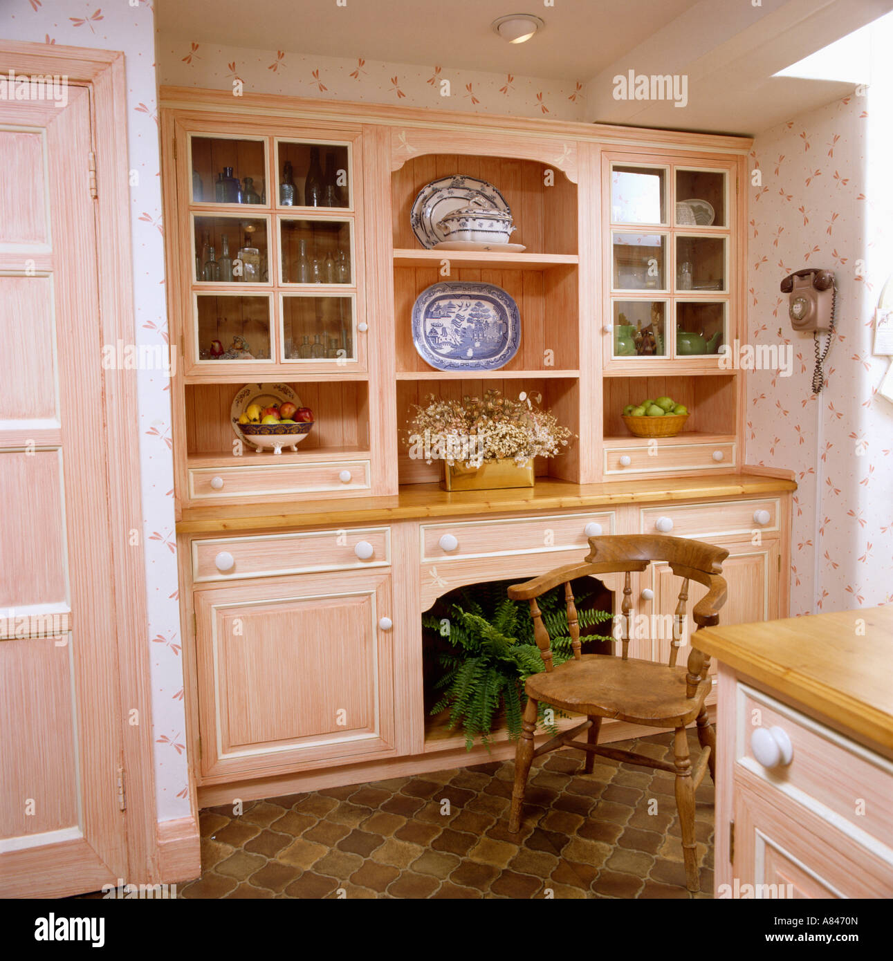 Wooden chair in front of built in dresser in peach traditional kitchen