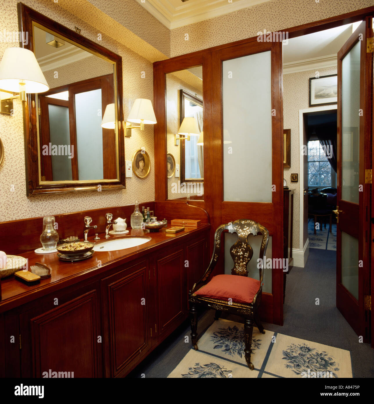 Traditional bathroom with wall-lights on either side of large framed ...