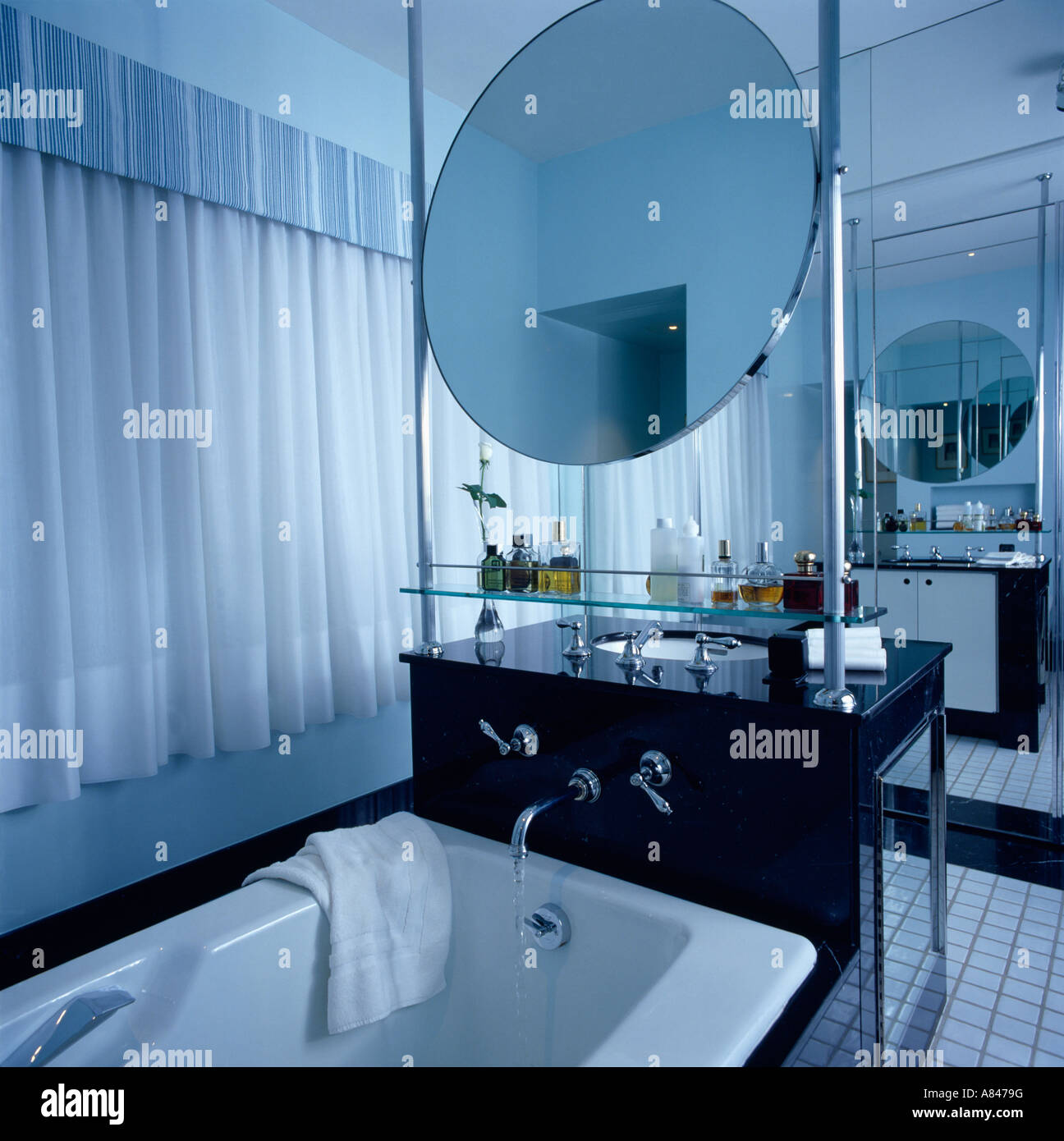 Circular mirror above bath in modern black and white bathroom Stock ...
