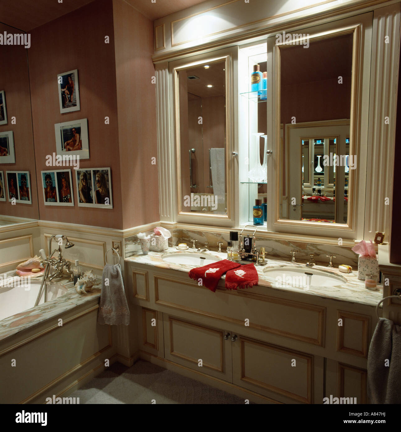 Double mirrors above double basins in vanity unit in town bathroom - Stock Image