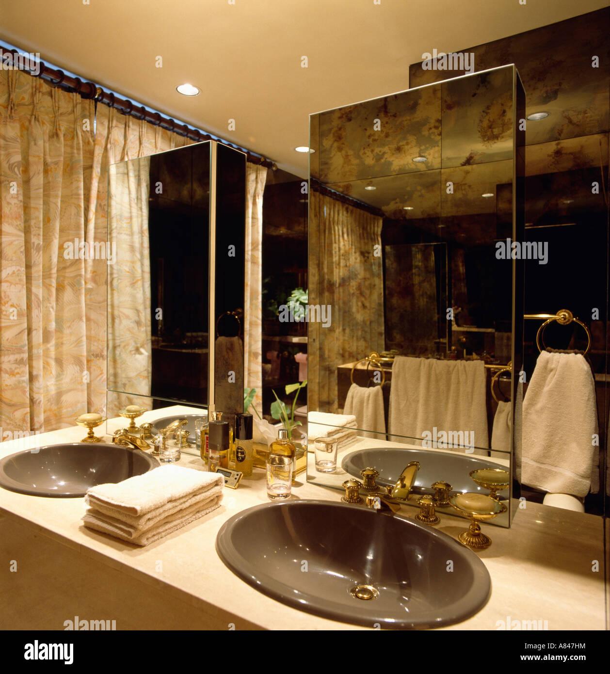 Brown plastic oval basins in vanity unit below mirror in town bathroom - Stock Image