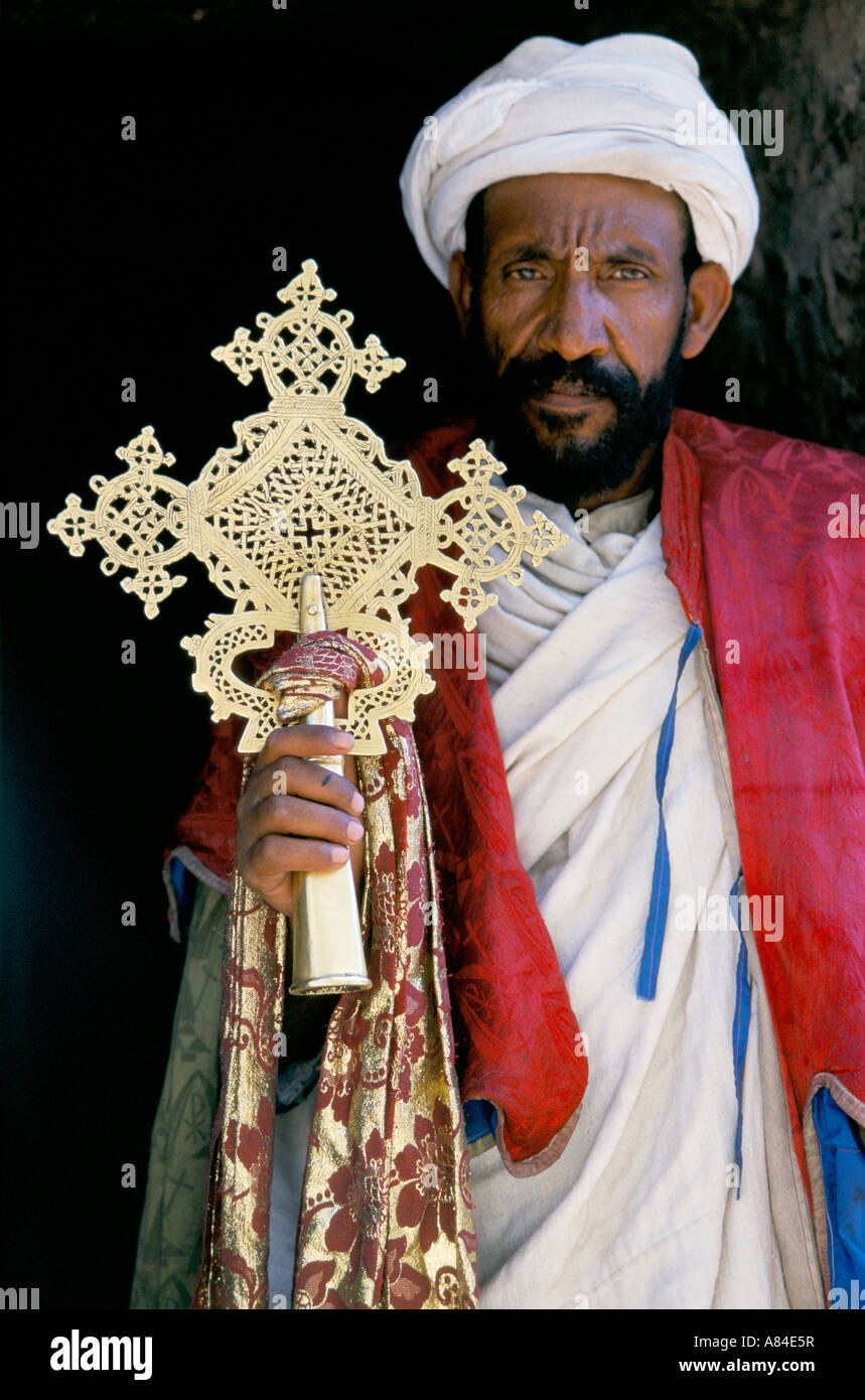 Ethiopian Orthodox Priest, outside a church at Lalibela holding an ornate brass cross. - Stock Image