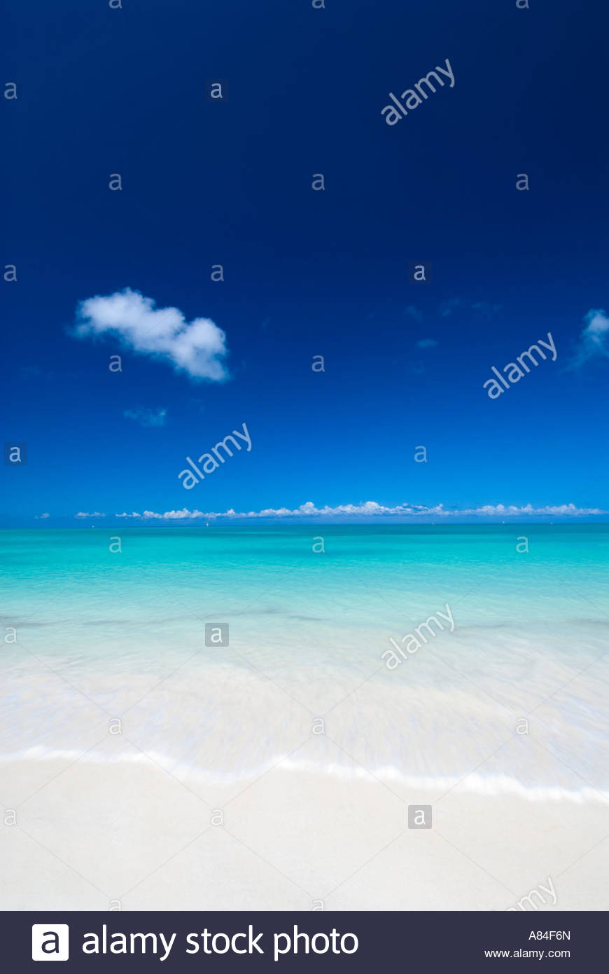 A classic view of turquoise seas and white sand beach at Dickenson Bay, Antigua, Caribbean - Stock Image