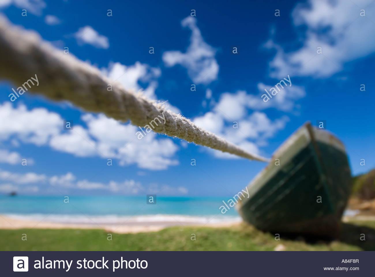 Close up of mooring rope tied to wooden fishing boat on beach Antigua, Leeward Islands, Caribbean - Stock Image
