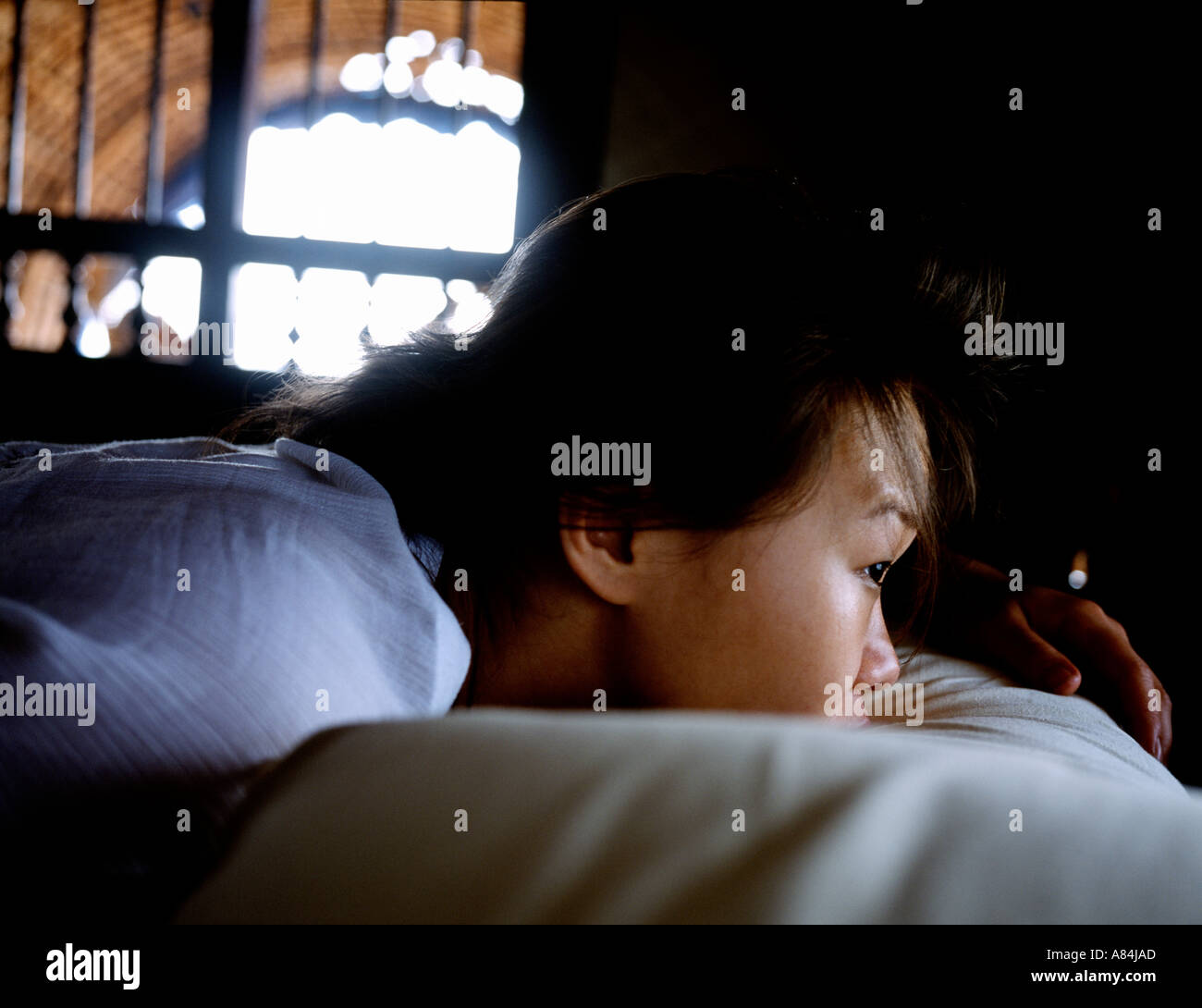 asian girl lying in bed  looking out window LOCATION - Stock Image