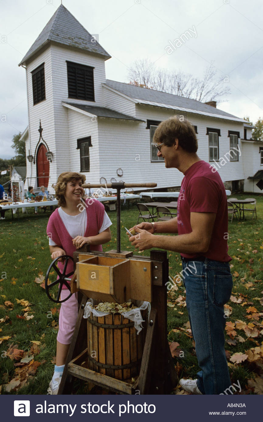 Couple pressing apples at the Apple Festival at St Luke s Church in Lanesborough Massachussets, USA - Stock Image