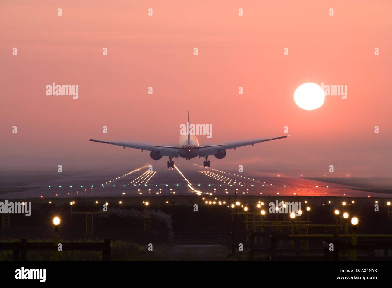 Aeroplane landing at sunrise. - Stock Image