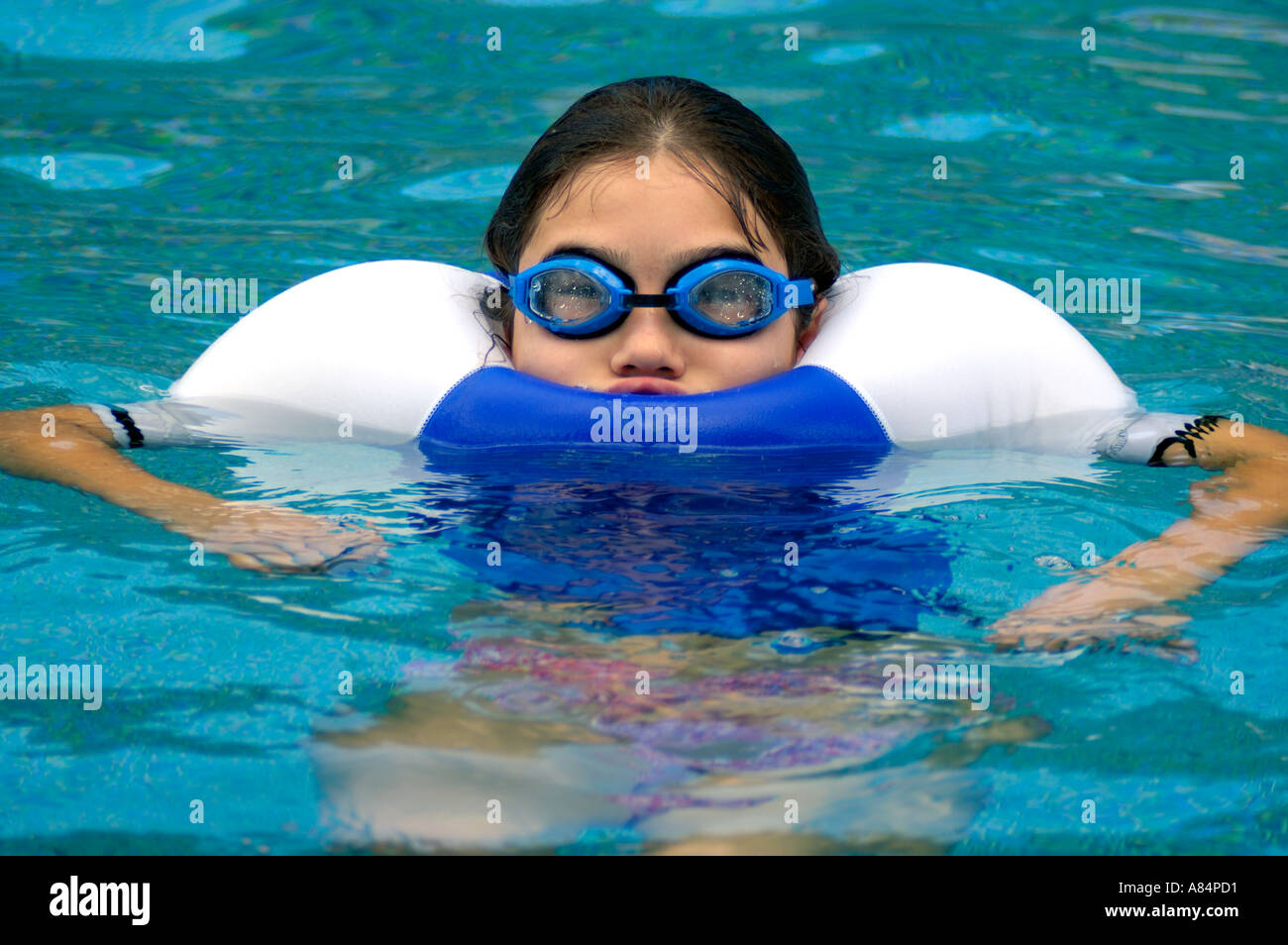 A playful young girl who is wearing googles and a rash guard blows up in the swimming pool  - Stock Image