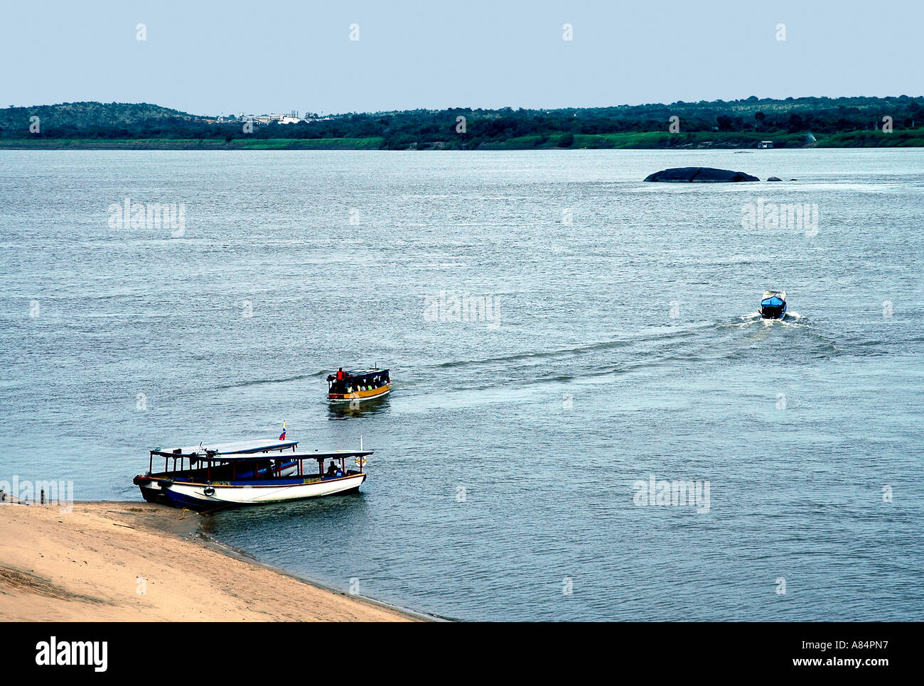 Small passenger boats ferry people across the Orinoco river at Ciudad Bolívar in Venezuela - Stock Image