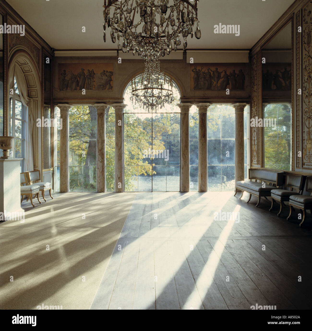 Sunlight floor-boards in large hall with antique glass chandeliers and tall  arched windows with view of gardens - Sunlight Floor-boards In Large Hall With Antique Glass Chandeliers