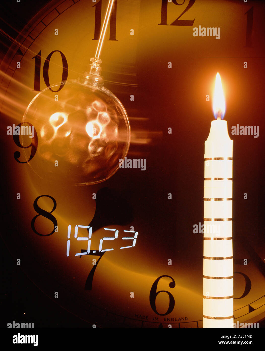 Time concept. Still life of swinging pendulum, candle and clockface. - Stock Image