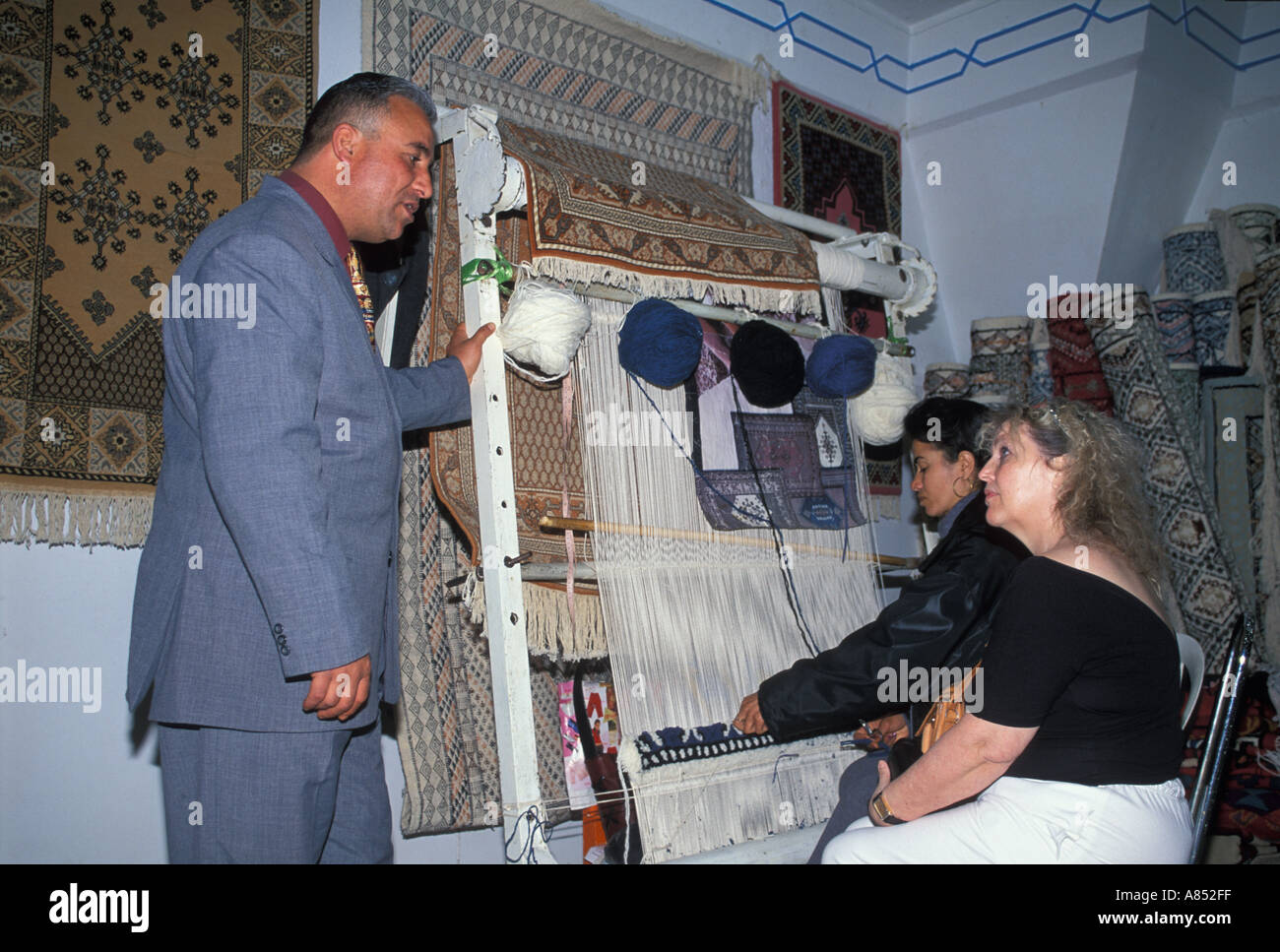 Man and woman carpet factory medina Souse Tunisia - Stock Image