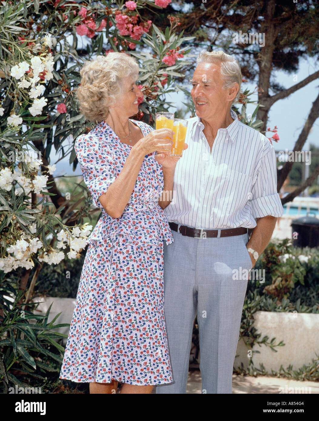 Retirement age couple on vacation, standing with glasses of orange juice on outdoor terrace. Stock Photo