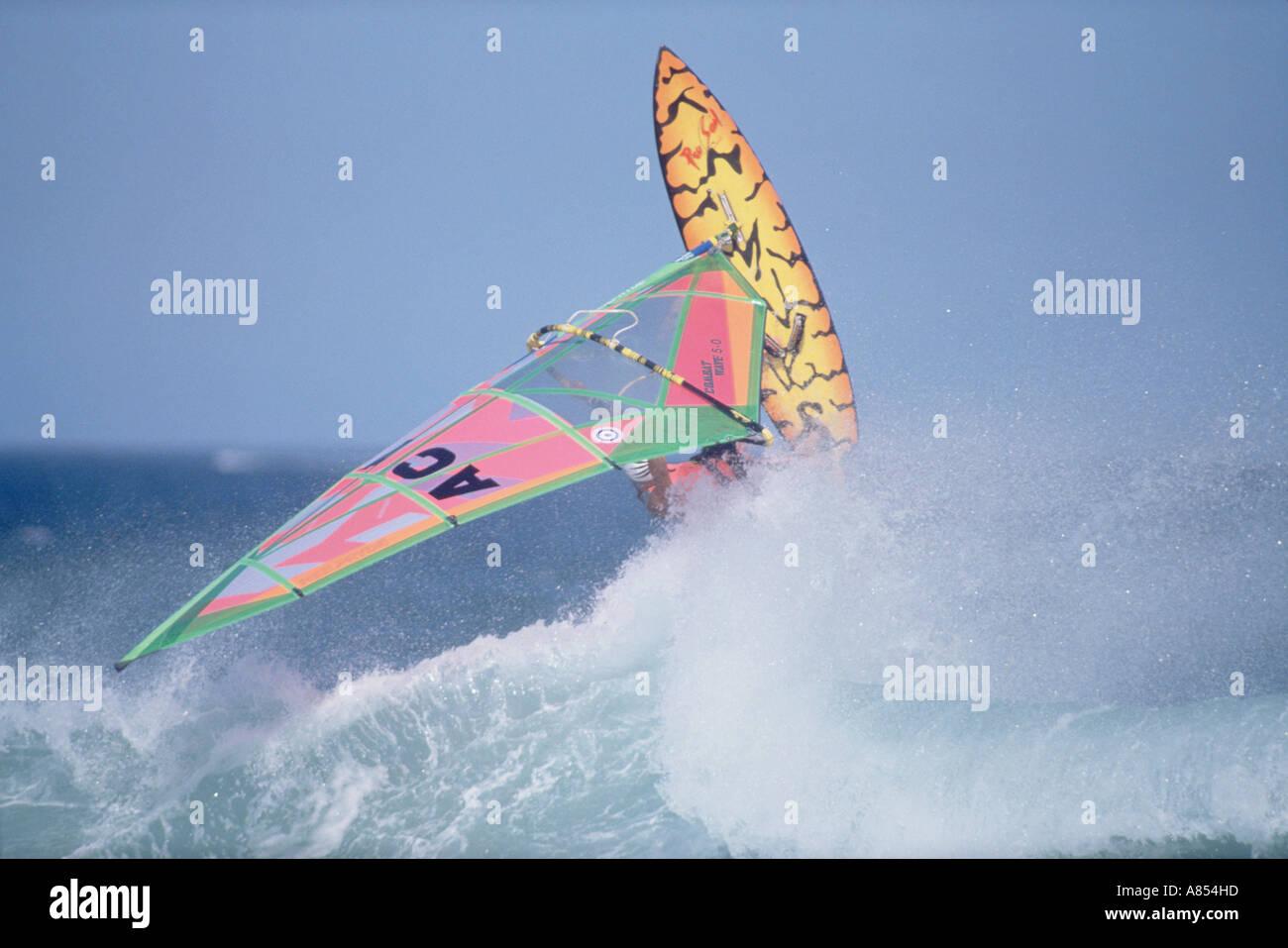 Windsurfing sailboard jumping ocean wave Stock Photo