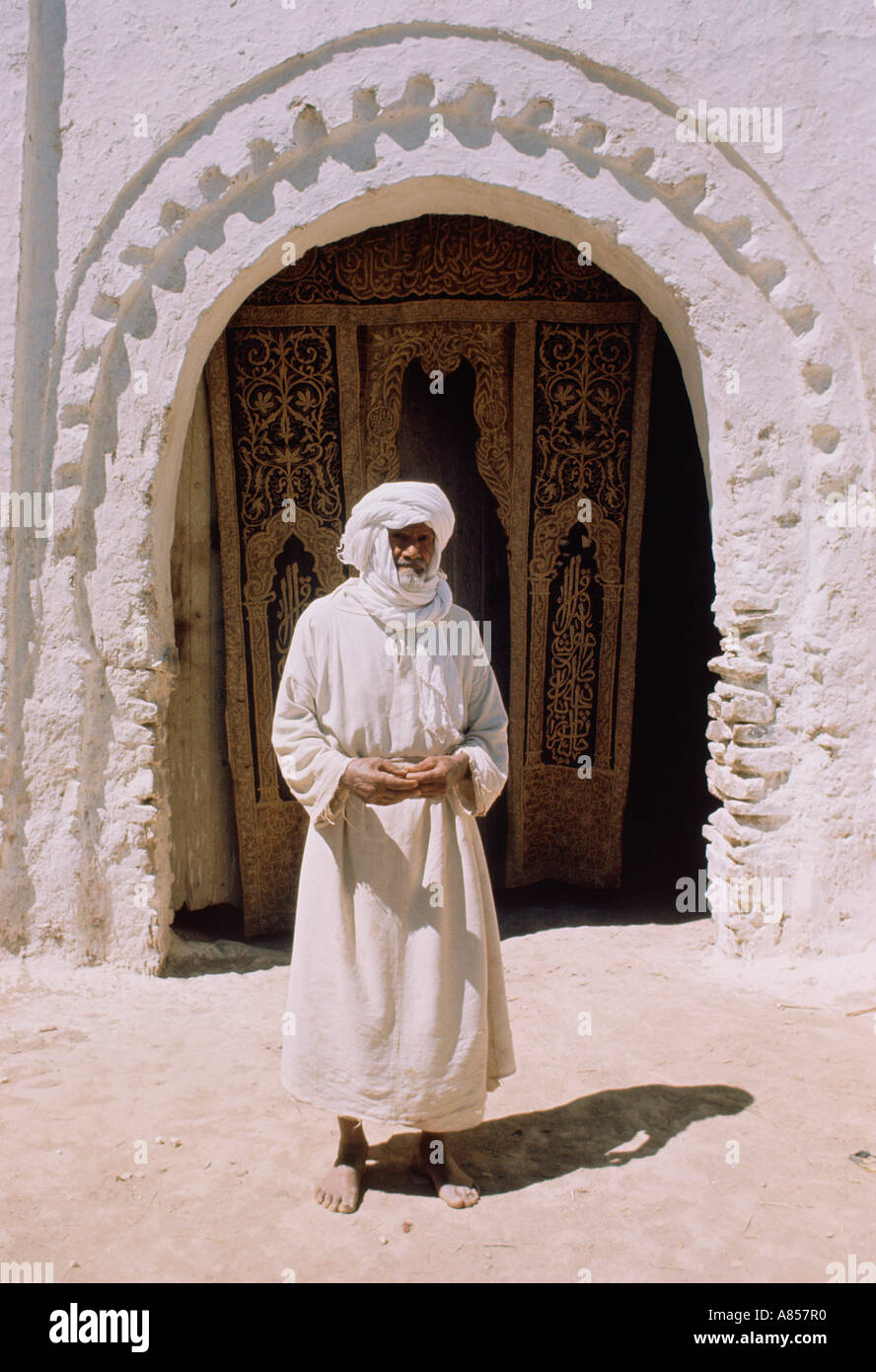 Morocco. Erfoud. Local man standing in front of Old city gate. - Stock Image