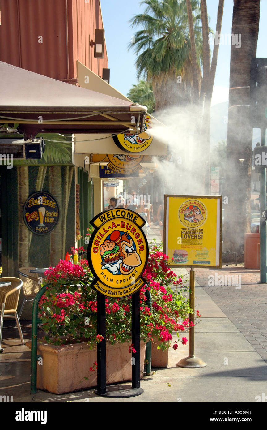 An outdoor burger shop with mist generated to keep cool on East Palm Canyon Drive Palm Springs California USA - Stock Image