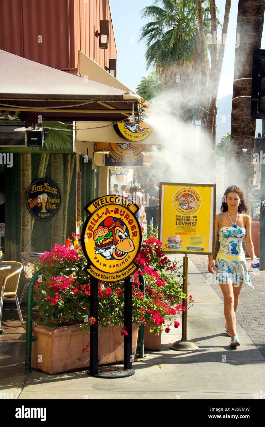 A girl walking by an outdoor burger shop with mist generated to keep cool on East Palm Canyon Drive Palm Springs - Stock Image