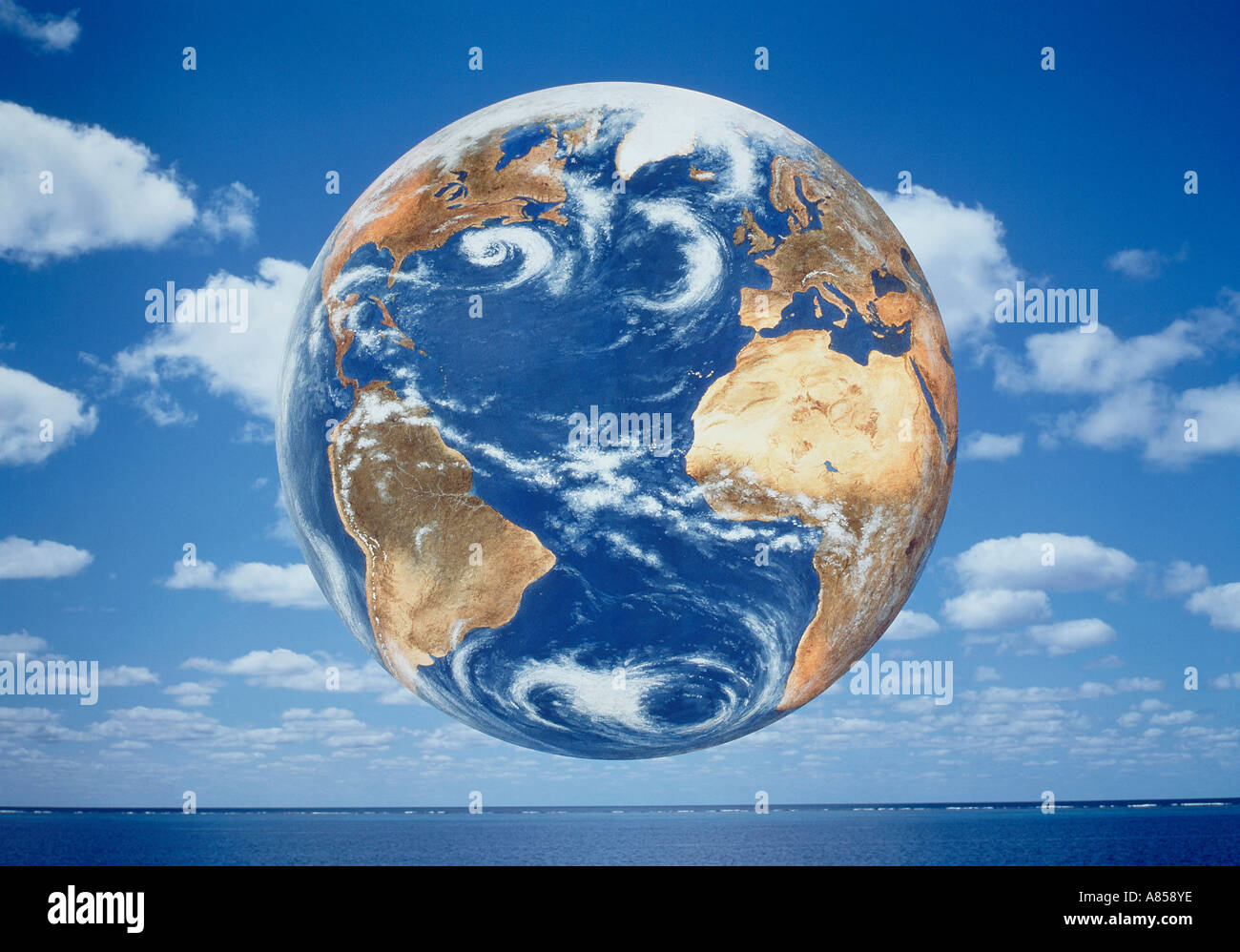 Concept illustration of planet Earth floating in blue sky above ocean horizon. - Stock Image