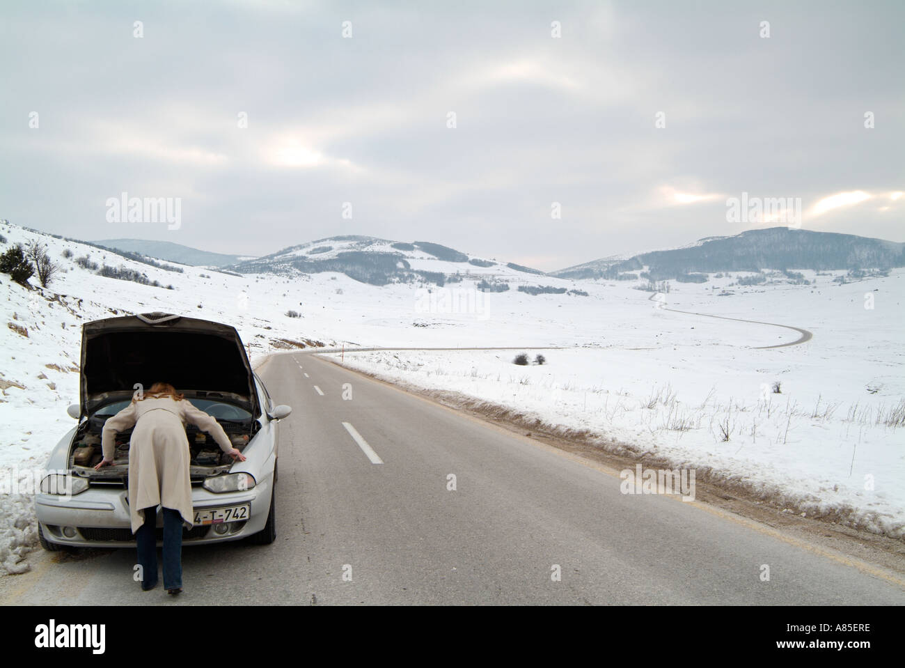Young Woman Looking Under The Bonnet Of Her Car After Being Stranded On An Isolated Road In Winter After A Break - Stock Image