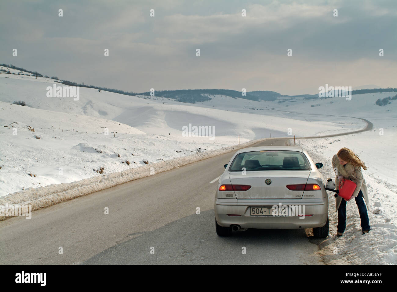 Woman Refilling Her Car with Petrol After Breaking Down on an Isolated Rural Road in Winter - Stock Image