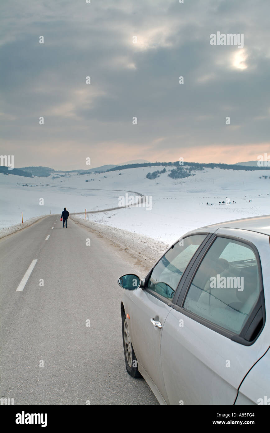 Man Leaves His Spouse in the Car to Walk Along an Isolated Road in a Snow Covered Valley in Search of Fuel - Stock Image