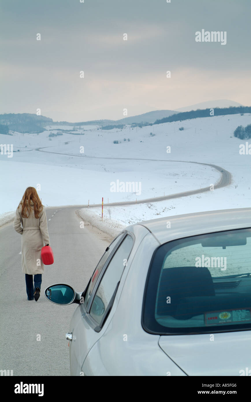 Woman Starts the Long Walk Along an Isolated Country Road in Winter to Find Fuel for Her Broken Down Car - Stock Image