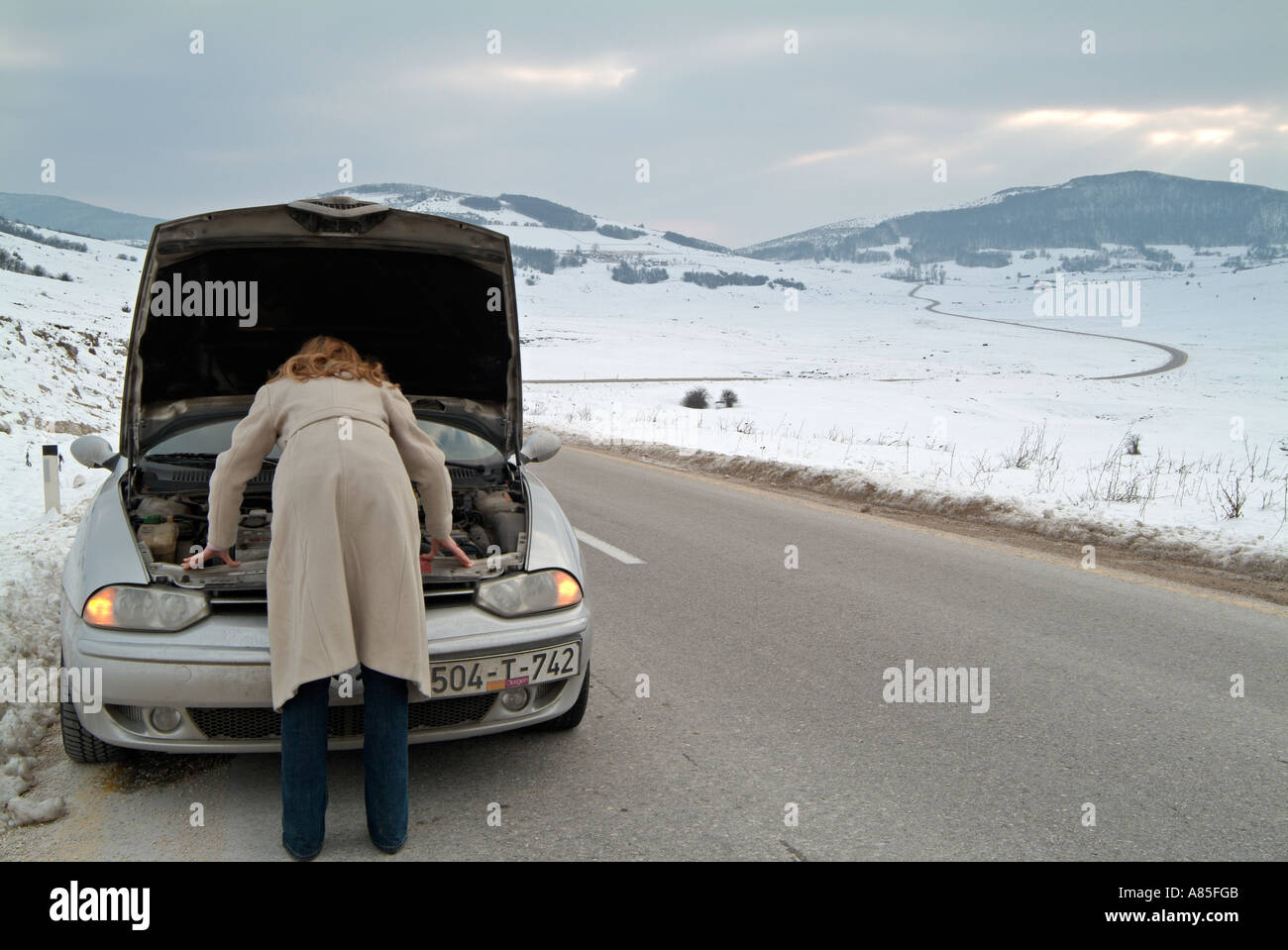 Young Woman Looking Under the Bonnet of Her Car after being Stranded on an Isolated Road in Winter After A Break Down - Stock Image