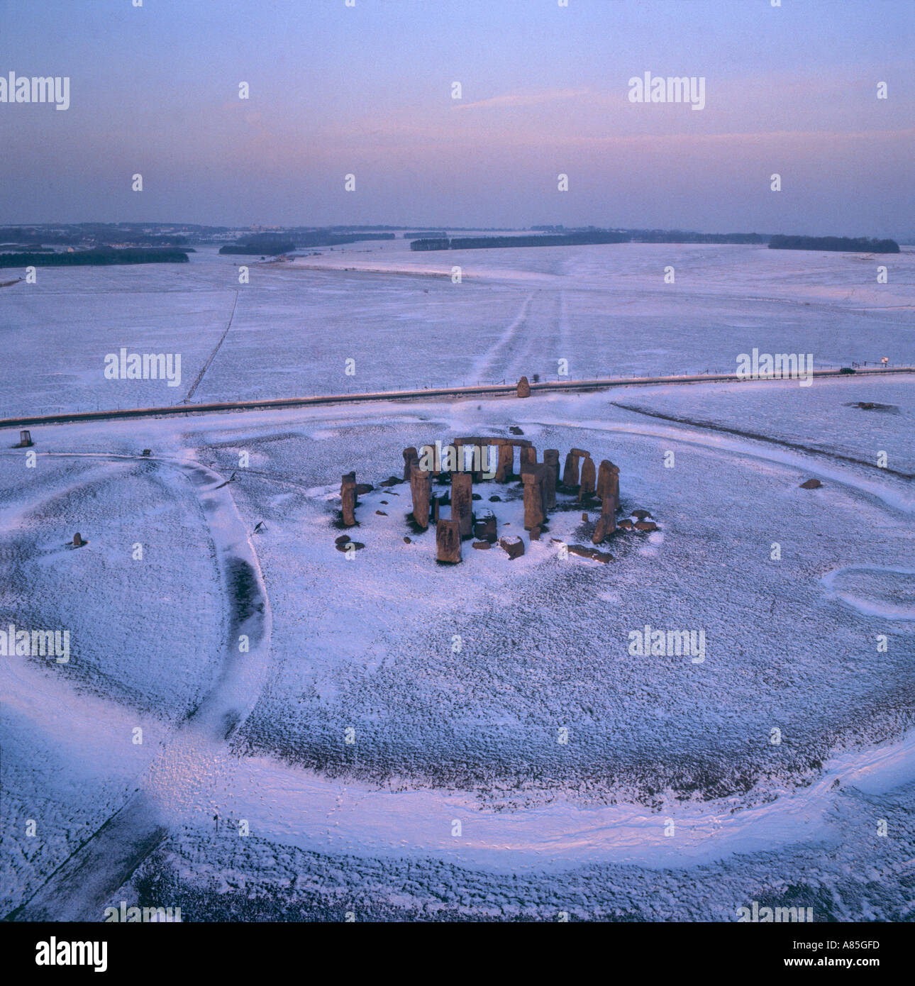 Stonehenge in sunset snow Wiltshire aerial view with The Avenue processional route in background Stock Photo