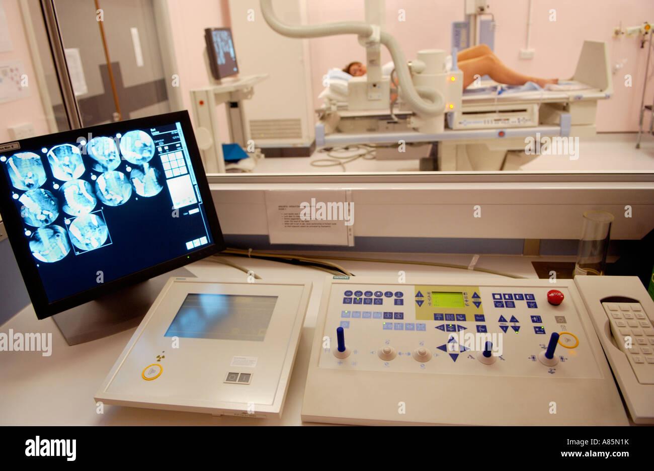 Woman having barium enema on table of Siemens Medical Solutions Axiom Iconos R200 fluoroscopy imaging unit private - Stock Image