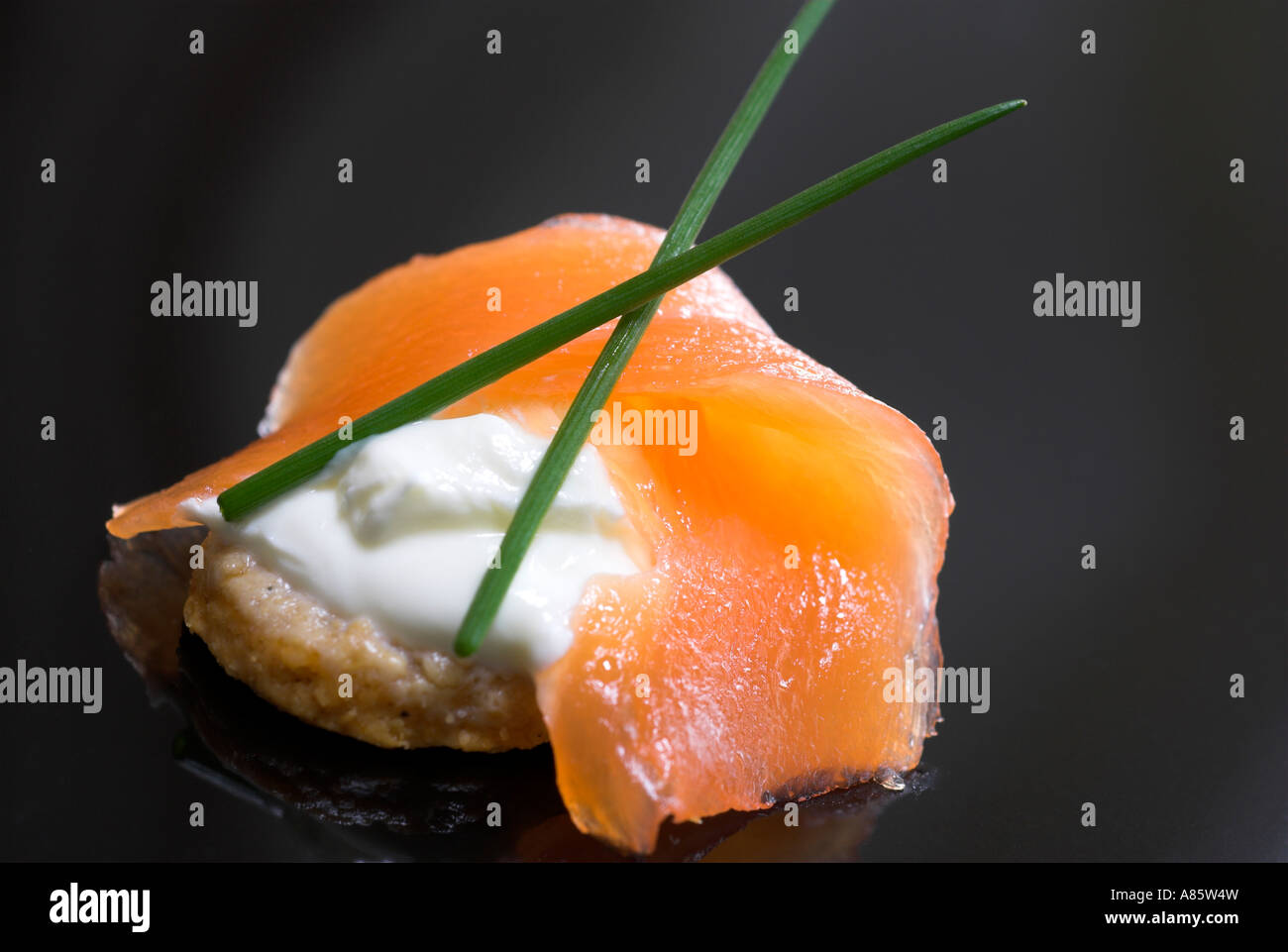 Smoked salmon canapes on a black plate. - Stock Image