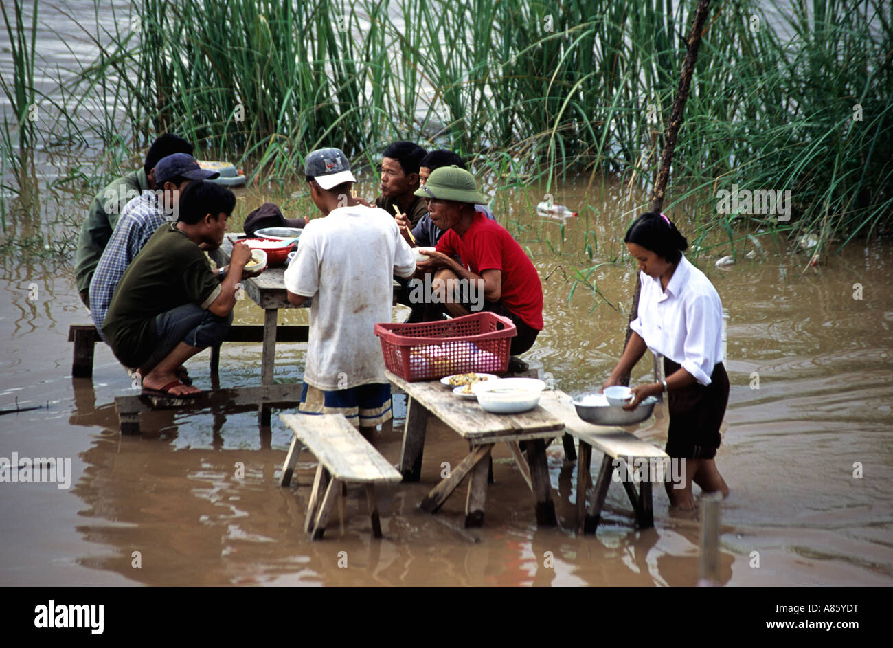 Waitress serving lunch at a flooded restaurant in Vientiane,Laos. Mekong River. - Stock Image
