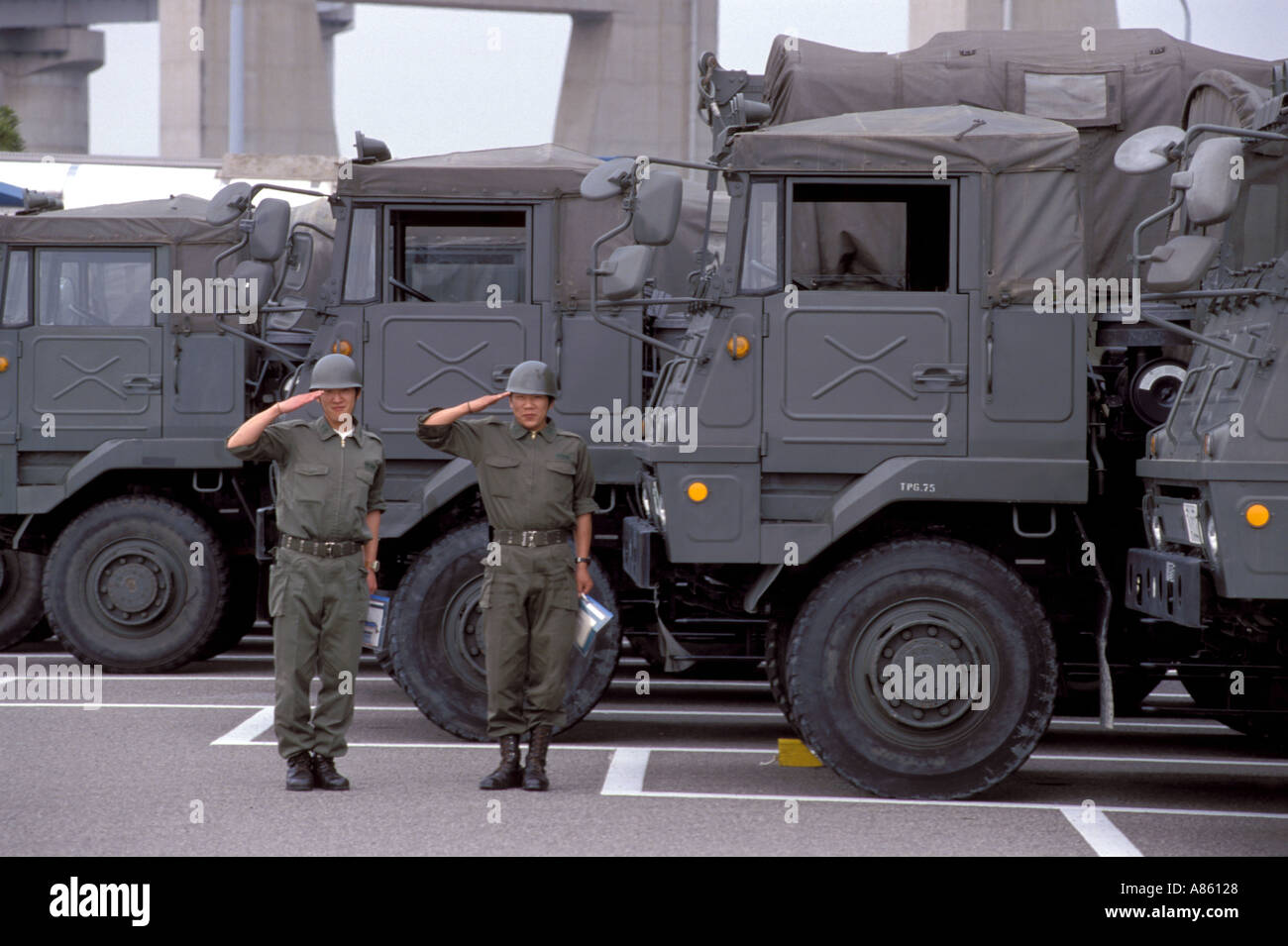 Two soldiers in uniform from Japan's national defense forces salute while standing beside their military vehicles - Stock Image