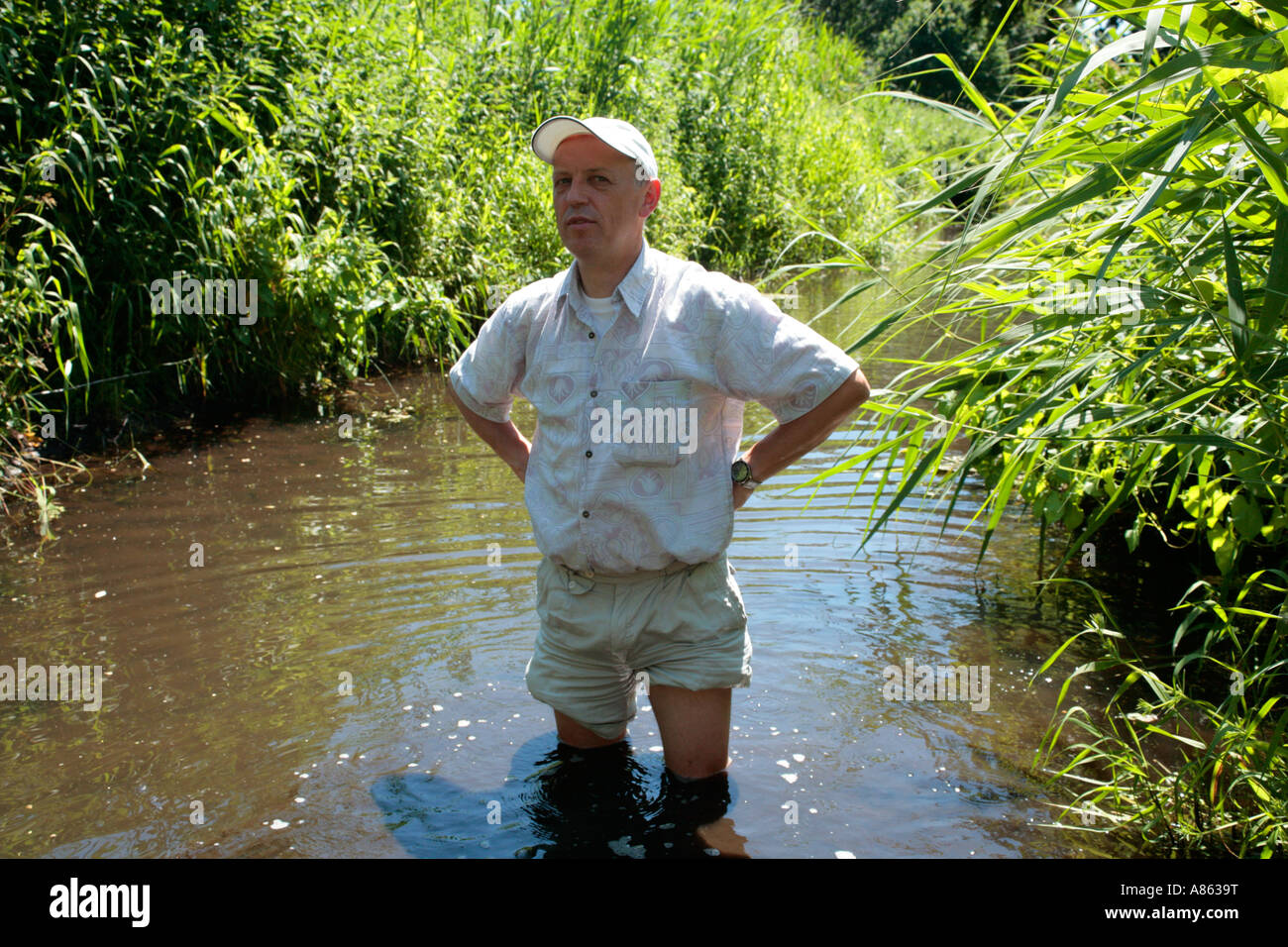 man with turned up trousers standing in a dirty river - Stock Image