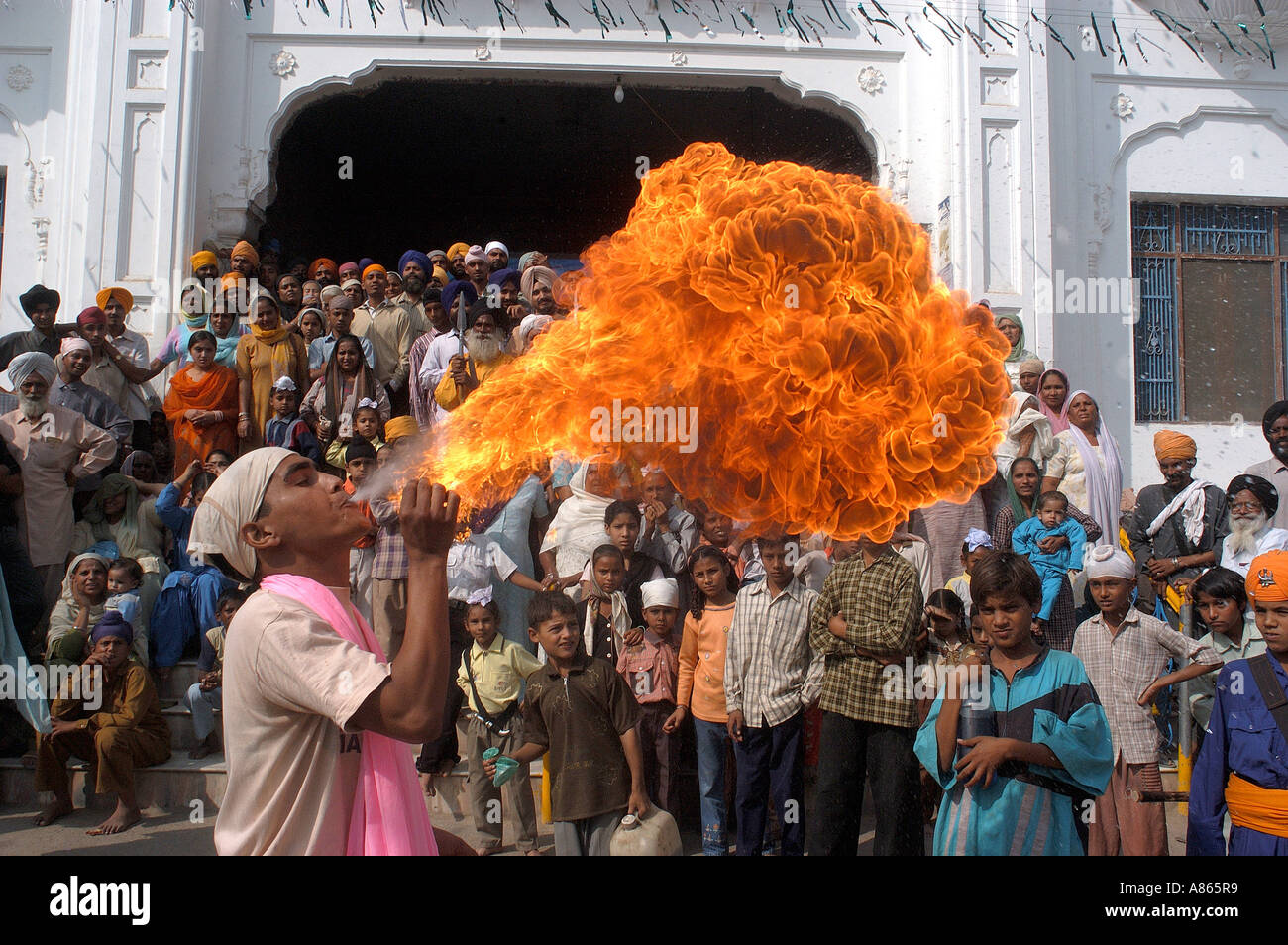 Man performing art of blowing fire from his mouth at Baba Bakala a small town in the Amritsar district of Punjab - Stock Image