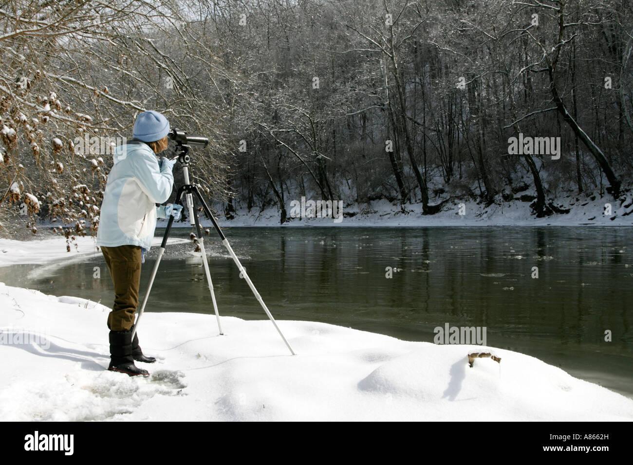 Winter Birdwatcher using Spotting Scope - Stock Image