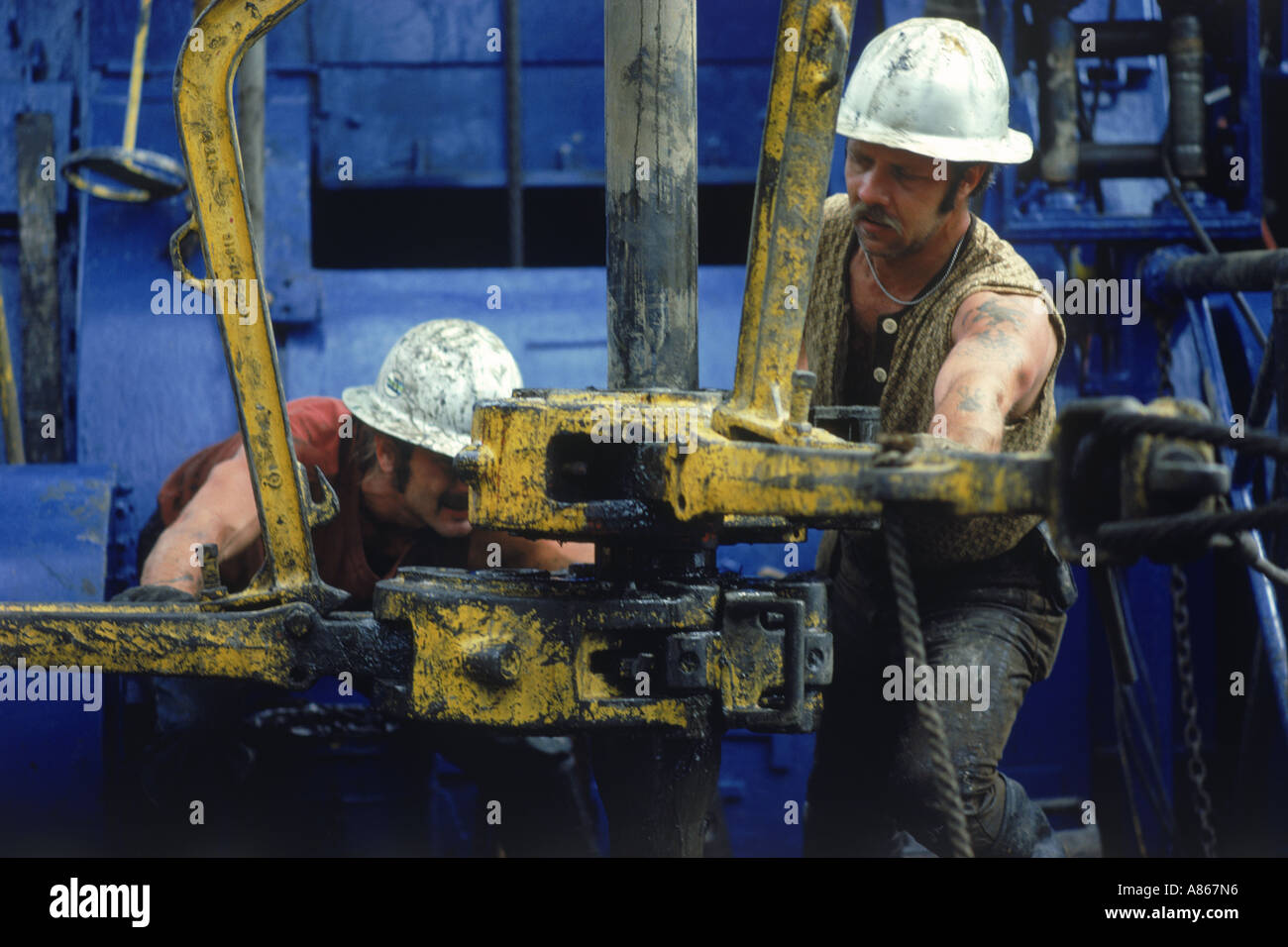 Men working on offshore oil rig coupling drill bits Stock Photo