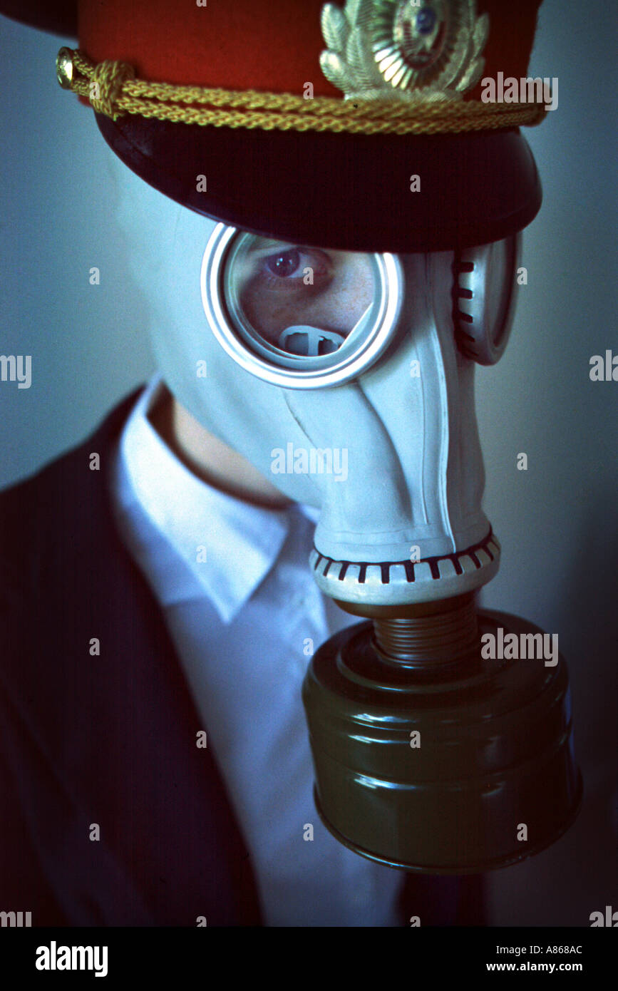 A female model in a gas mask business suite and KGB officer hat - Stock Image