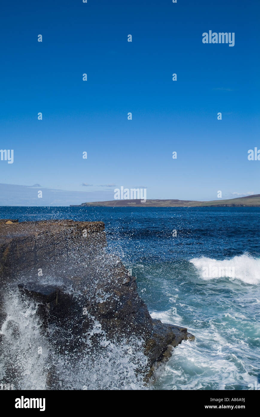 dh Eynhallow Sound EVIE ORKNEY Rolling waves splashing ashore seacliff blue sea and Rousay island coast Stock Photo