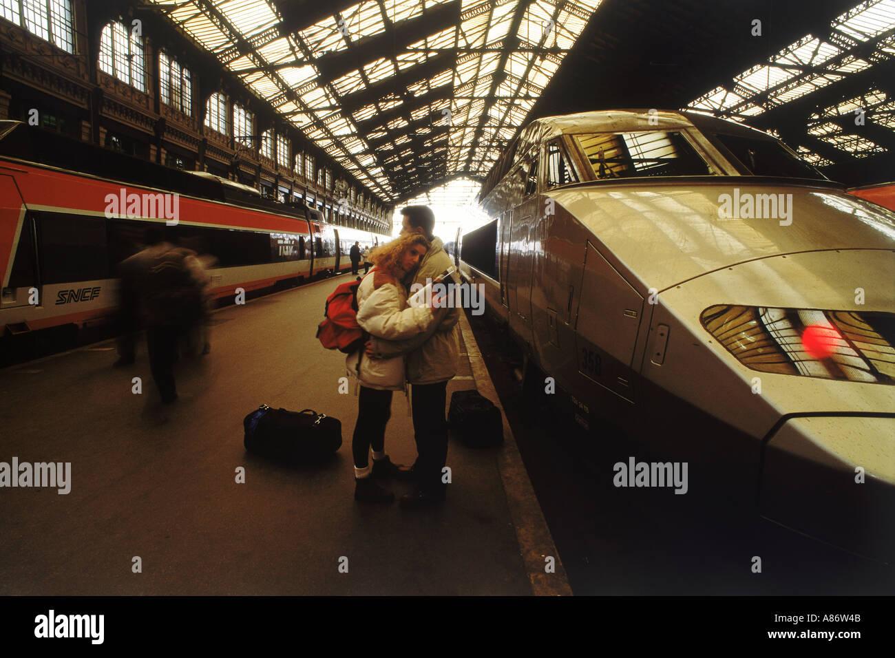 Couple saying goodbye next to SNCF high speed train at Gare du Lyon in Paris - Stock Image