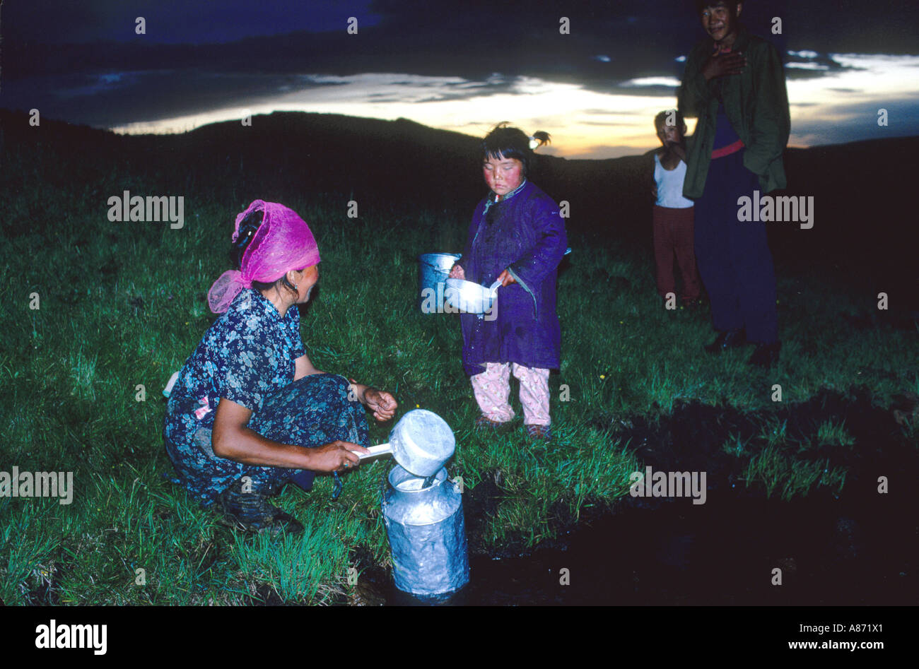 Mongolia fetching water from a brook in the evening in the province of Khoevsgoel Stock Photo