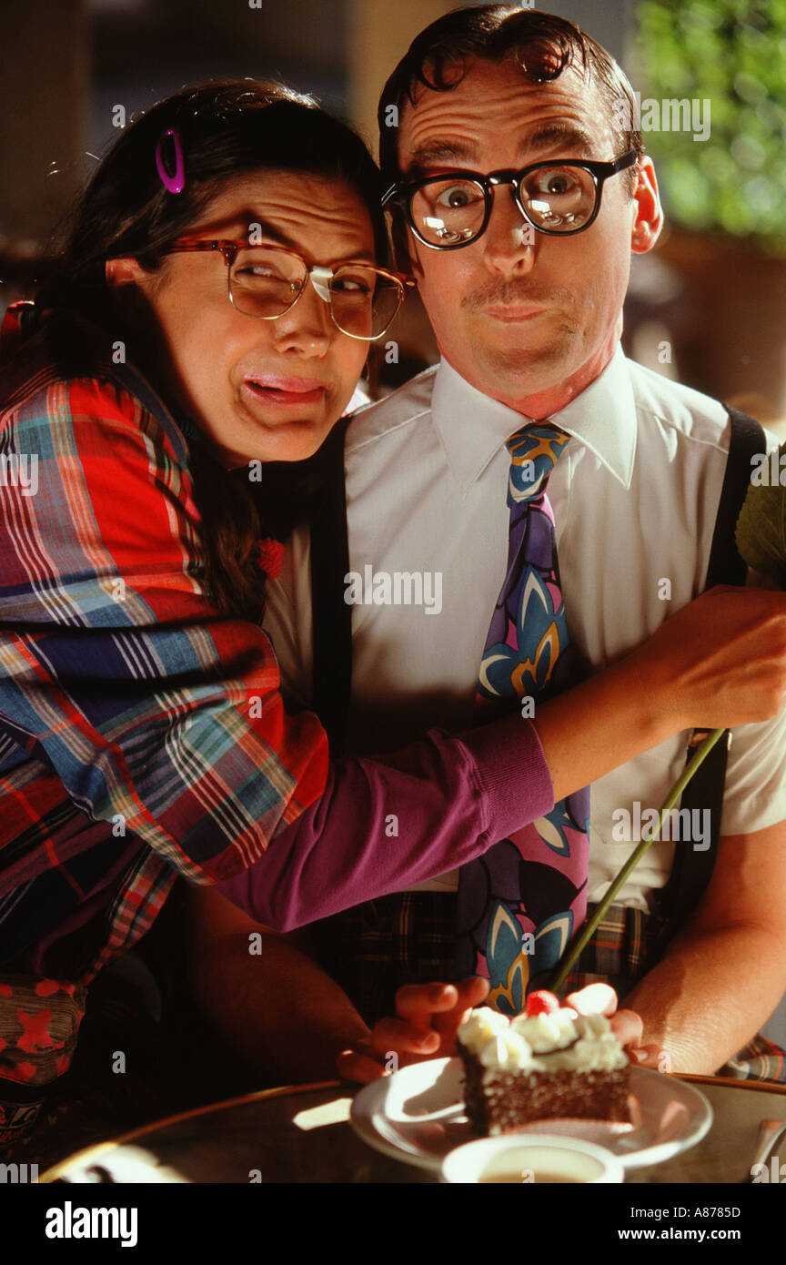 A young man and woman wearing intentionally nerdy black rim glasses scientist shirt tie making nerdy faces sitting Stock Photo