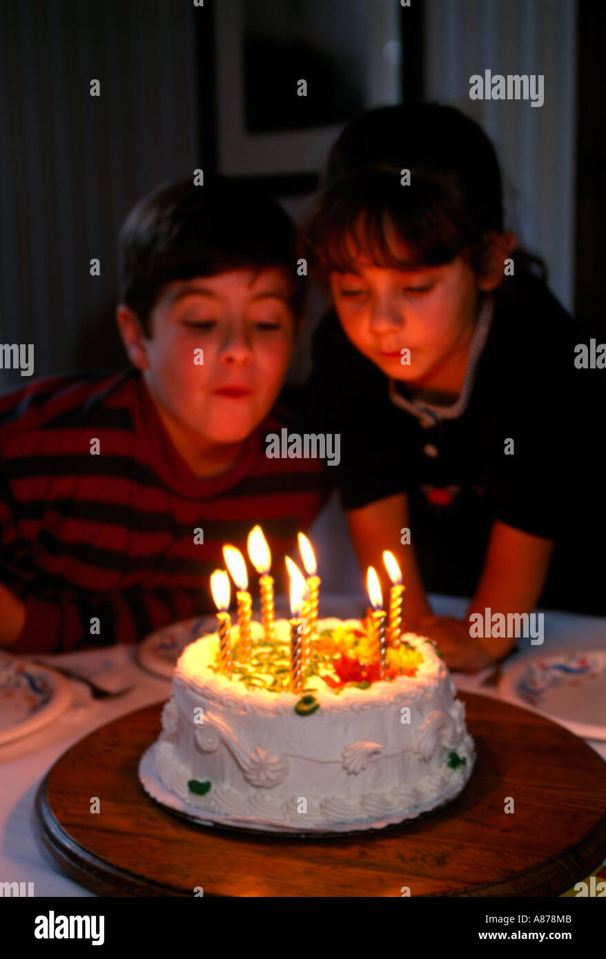 Brother And Sister Blowing Out Candles On Birthday Cake Stock Photo
