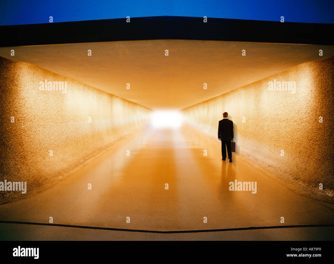 Businessman with briefcase walking down corridor toward baggage claim and ground transportation at an airport - Stock Image