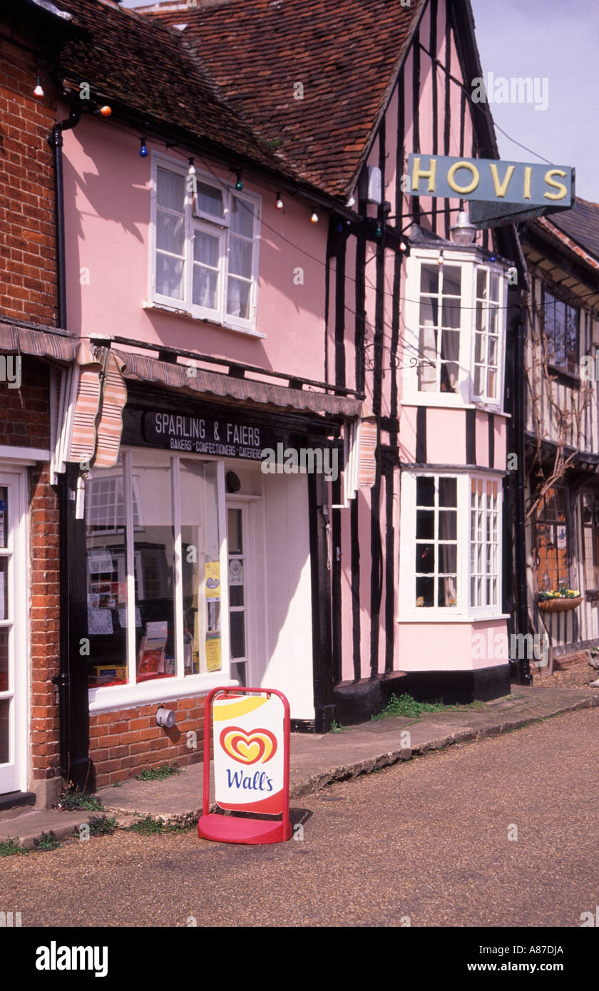 Timber framed buildings and village shops with Hovis sign on the market square Lavenham Suffolk - Stock Image