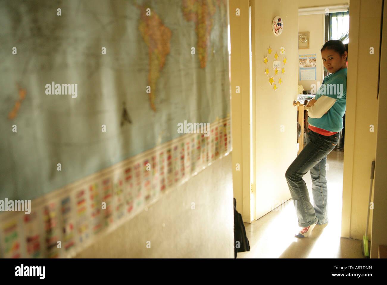 Teenage girl (15-17) leaning on doorframe - Stock Image