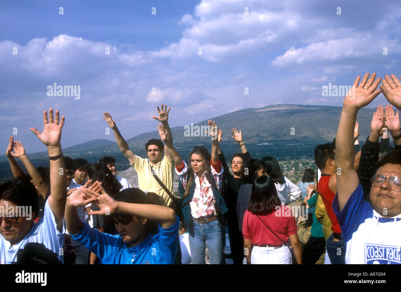People receiving energy with their arms up on first January on the top of the Pyramid of the sun, Mexico Stock Photo