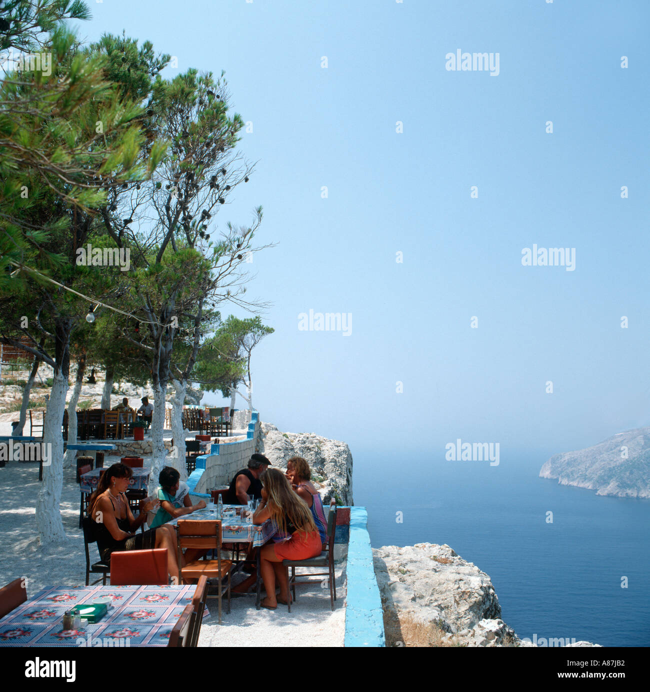 People enjoying a drink in a taverna in Kambi, West Coast ...