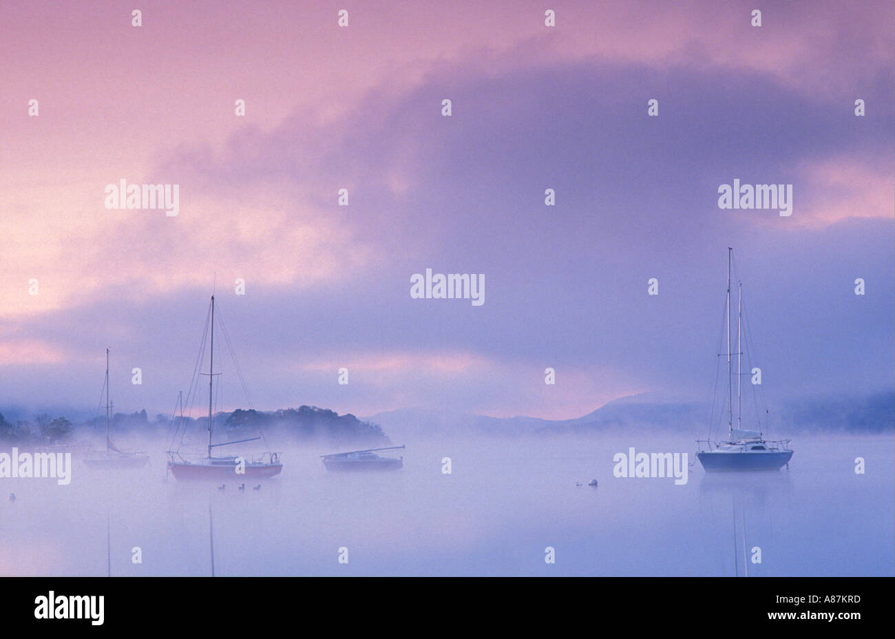Boats on Windermere at dawn Bowness on Windermere Lake District National Park Cumbria England UK - Stock Image