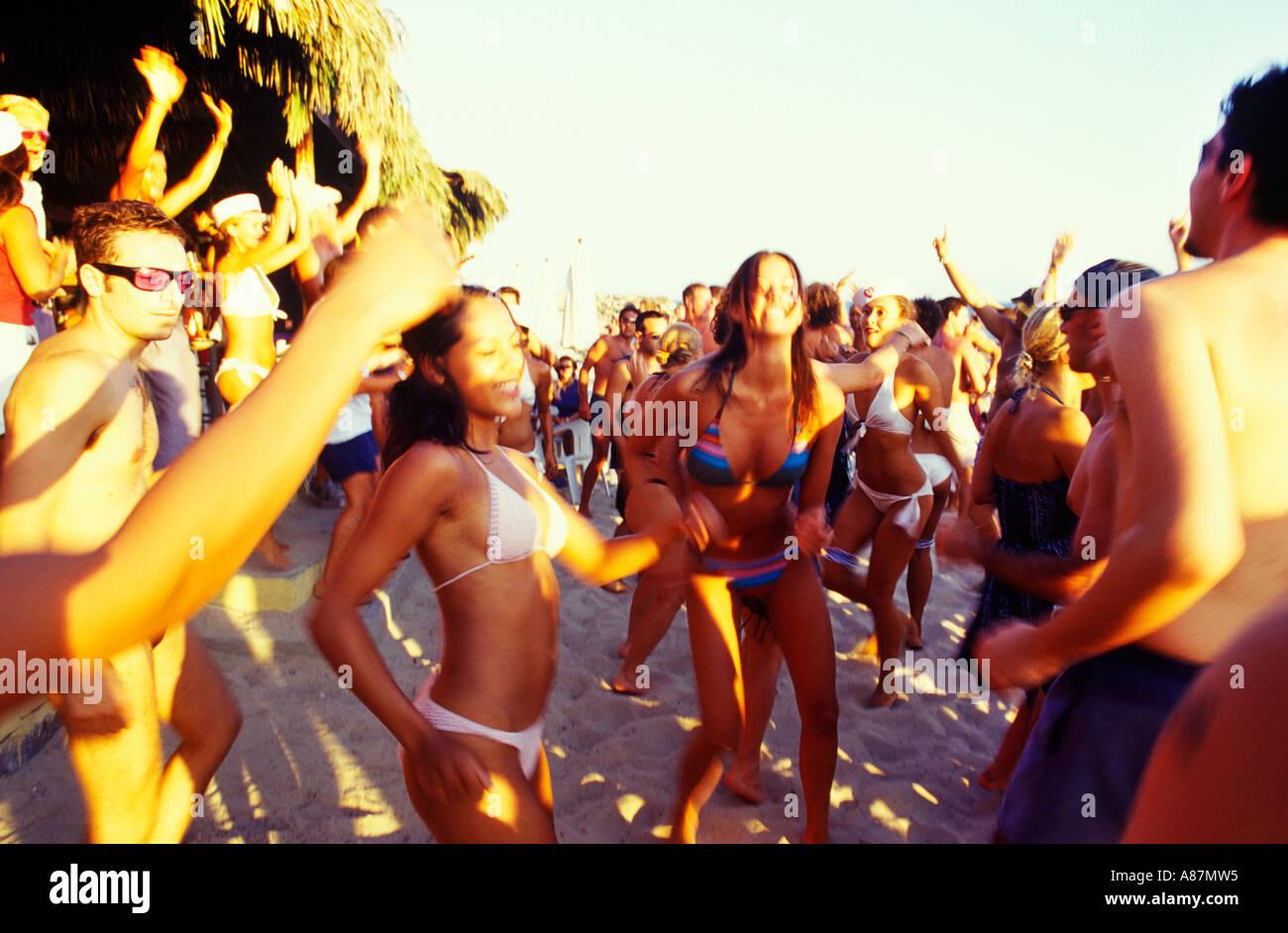 Girls dancing on Sa Trinchas beach Ibiza - Stock Image